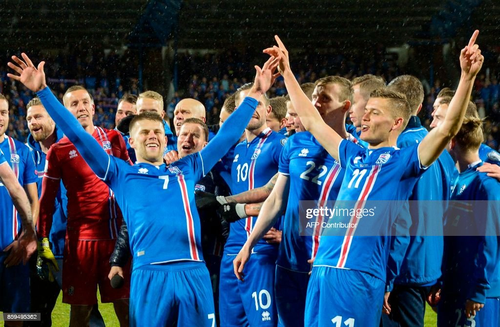 TOPSHOT - Iceland's players including Iceland's forward Johann Berg Gudmundsson (L) and Iceland's forward Alfred Finnbogason celebrate after the FIFA World Cup 2018 qualification football match between Iceland and Kosovo in Reykjavik, Iceland on October 9, 2017. Iceland qualified for the FIFA World Cup 2018 as smallest country ever after beating Kosovo 2-0 at home in Reykjavik. / AFP PHOTO / Haraldur Gudjonsson / ALTERNATIVE