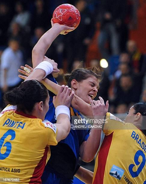Iceland's Stella Sigurdardottir fights for the ball with Romania's Aurelia Bradeanu and Crina Elena Pintea during their Women's EHF Euro 2012...