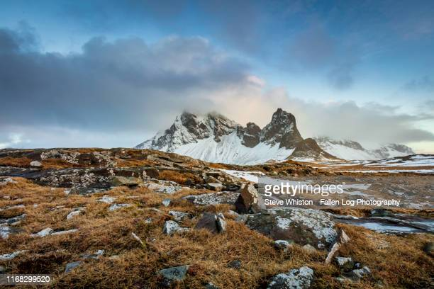 iceland's stokksnes mountains in winter with snow and rocks in foreground with blue sky - tundra stock pictures, royalty-free photos & images