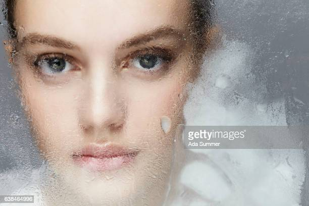 Iceprincess- close up of a female face behind a window