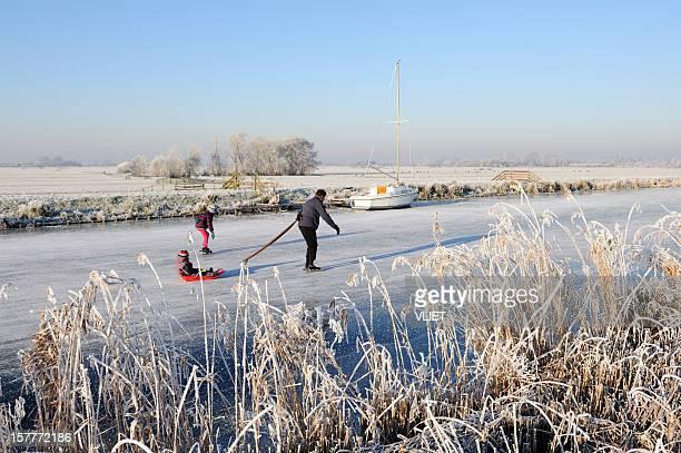 Eislaufen Erwachsene und zwei Kinder in einem gefrorenen Kanal