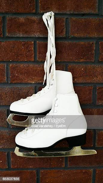 Ice-Skating Boots Hanging On Brick Wall