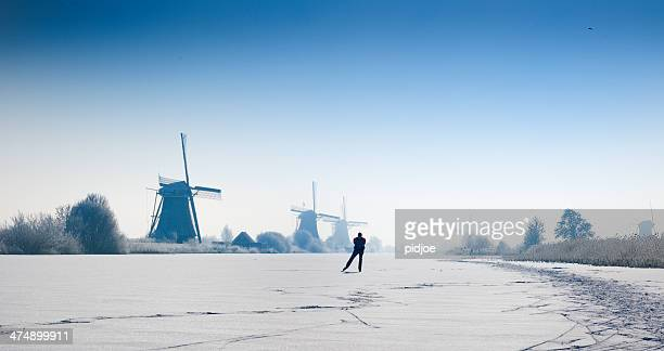ice-skating man on canal,near windmills kinderdijk winter time - ice skate stock pictures, royalty-free photos & images