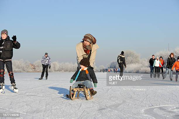 Ice-skating mother with son on a sled in the Netherlands