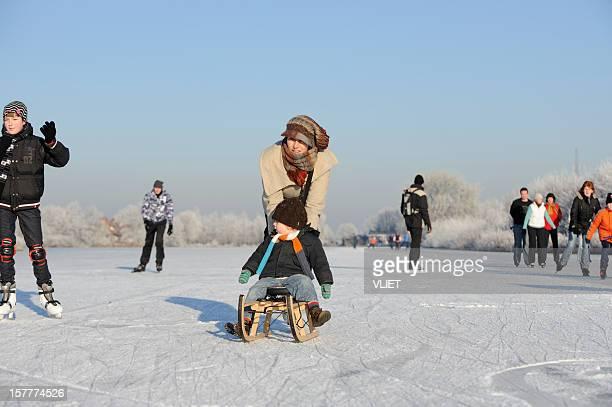 Patinaje sobre hielo madre con su hijo en un trineo en los Países Bajos