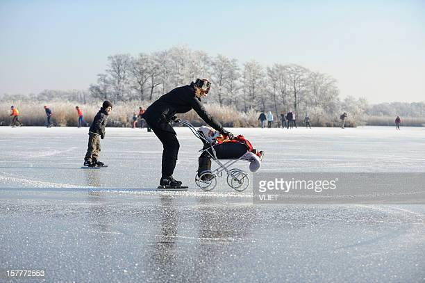 Ice-skating woman with baby stroller on a frozen lake