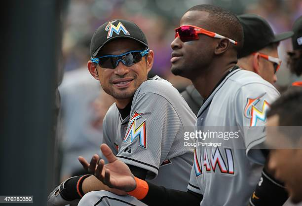 Ichiro Suzuki and Adeiny Hechavarria of the Miami Marlins look on from the dugout against the Colorado Rockies at Coors Field on June 7 2015 in...