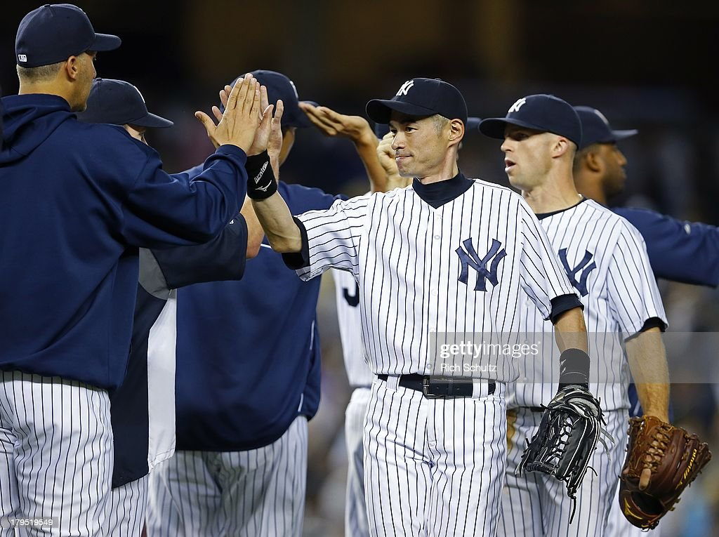 Ichiro Suzuki #31 and Brett Gardner #11 of the New York Yankees get high fives from teammates after the Yankees 6-5 win over the Chicago White Sox in a MLB baseball game at Yankee Stadium on September 4, 2013 in the Bronx borough of New York City.