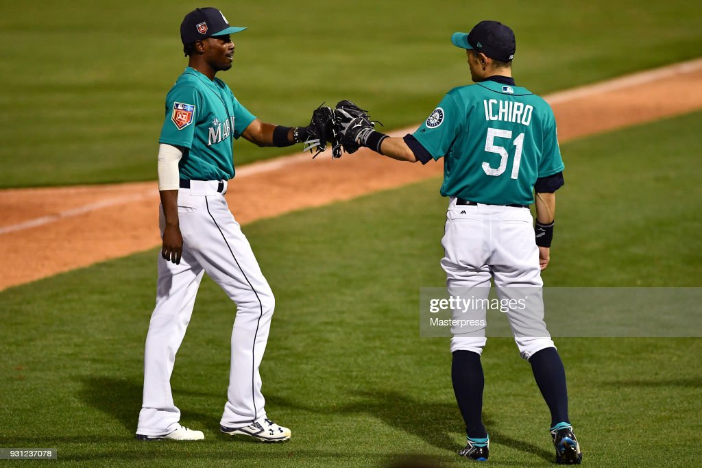 Ichiro Suzuki (R) and Dee Gordon of the Seattle Mariners touch fists during a spring training game between Seattle Mariners and Chicago White Sox on March 12, 2018 in Peoria, Arizona.