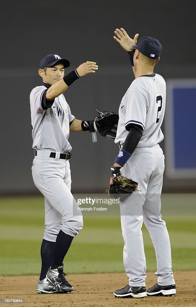 Ichiro Suzuki #31 and Derek Jeter #2 of the New York Yankees celebrate a win against the Minnesota Twins on September 24, 2012 at Target Field in Minneapolis, Minnesota. The Yankees defeated the Twins 6-3.