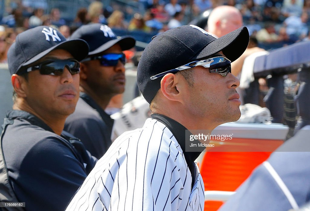 Ichiro Suzuki #31 and Hiroki Kuroda #18 (L) of the New York Yankees look on from the dugout against the Los Angeles Angels of Anaheim at Yankee Stadium on August 15, 2013 in the Bronx borough of New York City. The Angels defeated the Yankees 8-4.