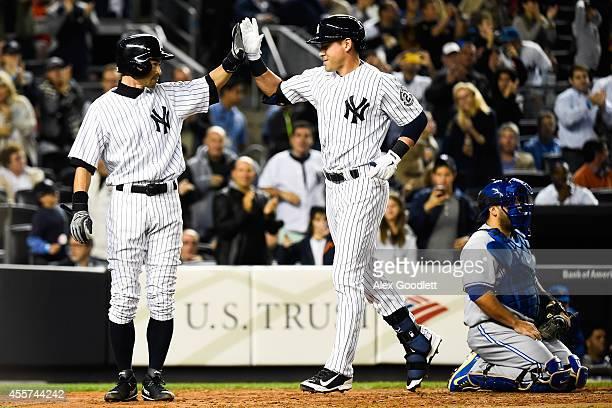 Ichiro Suzuki and Jacoby Ellsbury of the New York Yankees high five after scoring in the third inning against the Toronto Blue Jays at Yankee Stadium...