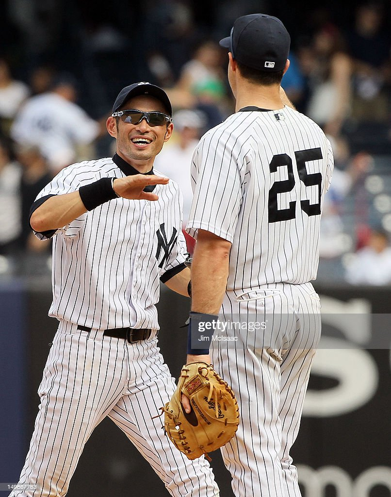 Ichiro Suzuki #31 and Mark Teixeira #25 of the New York Yankees celebrate after defeating the Seattle Mariners at Yankee Stadium on August 5, 2012 in the Bronx borough of New York City.