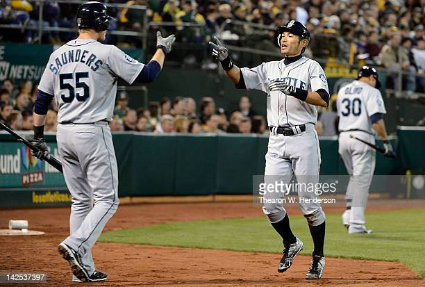 Ichiro Suzuki and Michael Saunders of the Seattle Mariners celebrates after Suzuki scored against the Oakland Athletics on Opening Day at Oco...