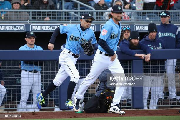 Ichiro Suzuki and Mike Leake of the Seattle Mariners run out onto the field during the first inning of the MLB spring training game against the...