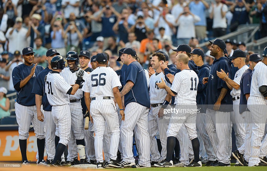 Ichiro Suzuki #31 celebrates with his team mates after his 4,000th career hit on a single in the 1st inning of the New York Yankees game against the Toronto Blue Jays at Yankee Stadium on August 21, 2013 in the Bronx borough of New York City.