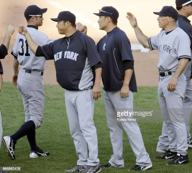 Ichiro Suzuki Hiroki Kuroda Masahiro Tanaka and manager Joe Girardi congratulate each other after the New York Yankees defeated the Chicago Cubs in...