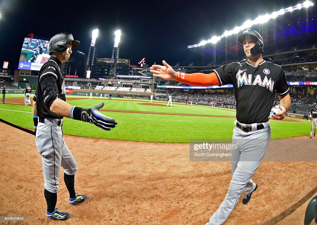 Ichiro Suzuki #51 of the Miami Marlins (L) congratulates Giancarlo Stanton #27 after scoring a ninth inning run against the Atlanta Braves at SunTrust Park on September 8, 2017 in Atlanta, Georgia.