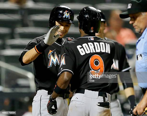 Ichiro Suzuki of the Miami Marlins congratulates teammate Dee Gordon after Gordon hit a home run in the ninth inning against the New York Mets on...