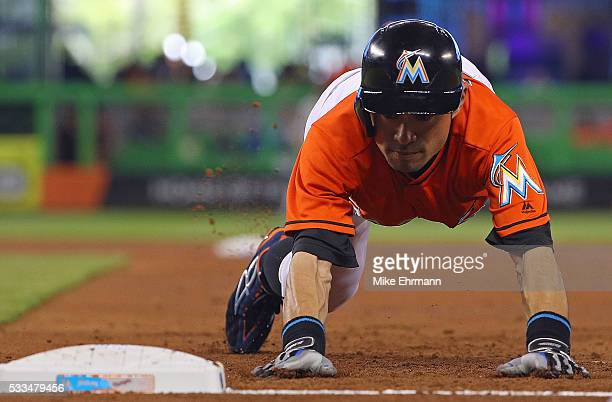 Ichiro Suzuki of the Miami Marlins dives back to first in the first inning during a game against the Washington Nationals at Marlins Park on May 22...