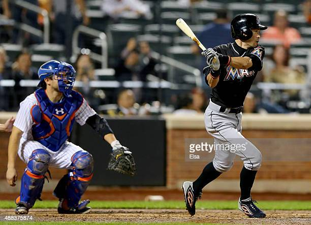 Ichiro Suzuki of the Miami Marlins hits a single in the ninth inning as Travis d'Arnaud of the New York Mets catches on September 15 2015 at Citi...