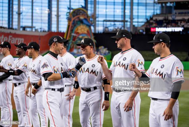 Ichiro Suzuki of the Miami Marlins interacts with Miguel Rojas David Phelps and Junichi Tazawa before the Opening Day game against the Atlanta Braves...