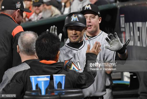 Ichiro Suzuki of the Miami Marlins is congratulated by teammates after he put down a sacrifice bunt against the San Francisco Giants in the top of...