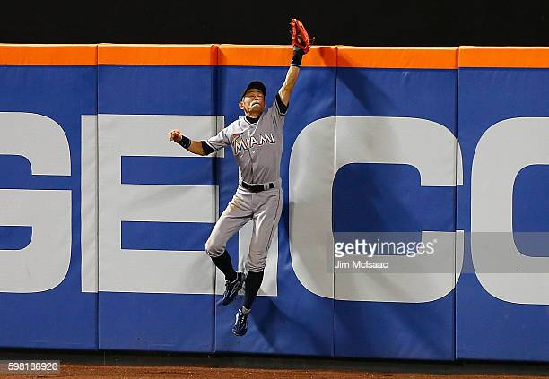 Ichiro Suzuki of the Miami Marlins makes a catch at the wall in the fifth inning on a ball hit by Curtis Granderson of the New York Mets at Citi...