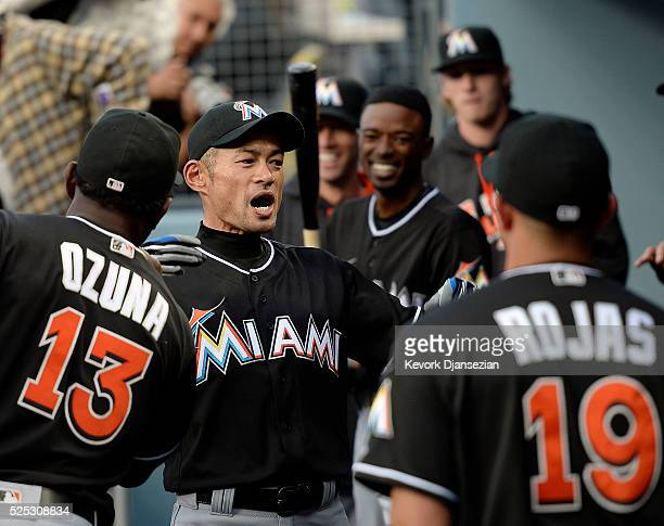 Ichiro Suzuki of the Miami Marlins motivates his teammates in the dugout at the start of a baseball game against Los Angeles Dodgers at Dodger...