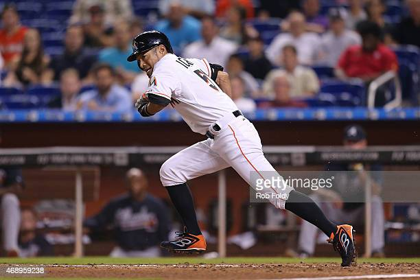 Ichiro Suzuki of the Miami Marlins runs to first base after bunting for a single during the seventh inning of the game against the Atlanta Braves at...