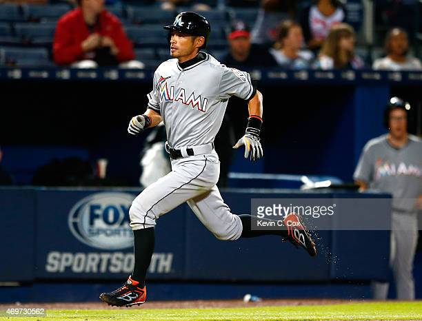 Ichiro Suzuki of the Miami Marlins scores on a double hit by Giancarlo Stanton in the eighth inning against the Atlanta Braves at Turner Field on...