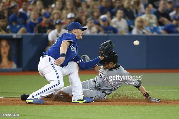 Ichiro Suzuki of the Miami Marlins slides into third base with an RBI triple in the fifth inning during MLB game action as Josh Donaldson of the...