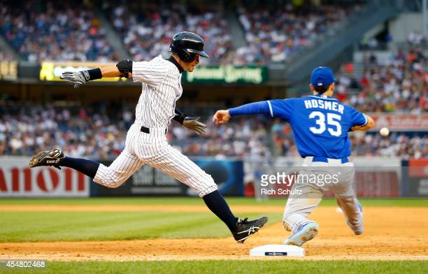 Ichiro Suzuki of the New York Yankees beats the ball to first base for a single before Eric Hosmer of the Kansas City Royals can catch it during the...