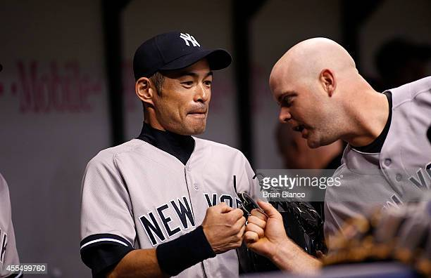 Ichiro Suzuki of the New York Yankees bumps fists with teammate Brian McCann in the dugout before the start of a game against the Tampa Bay Rays on...