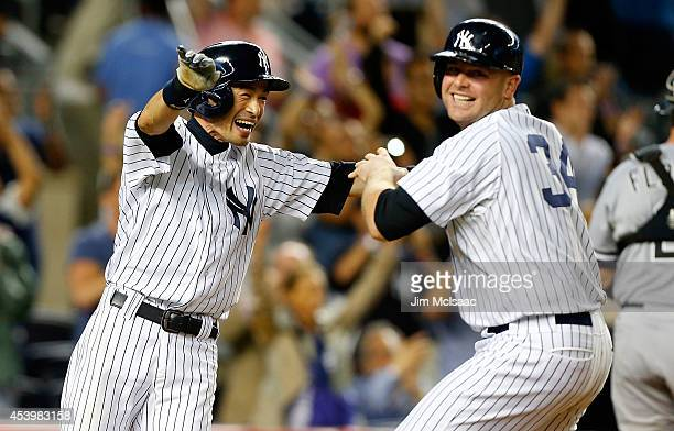 Ichiro Suzuki of the New York Yankees celebrates after scoring the game winning run against the Chicago White Sox in the ninth inning with Brian...