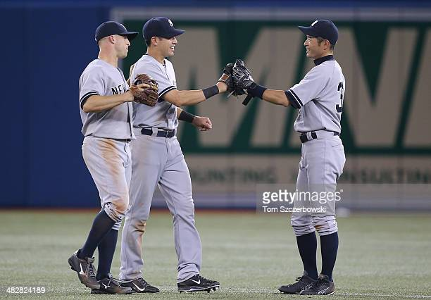 Ichiro Suzuki of the New York Yankees celebrates their victory with Jacoby Ellsbury and Brett Gardner during MLB game action against the Toronto Blue...