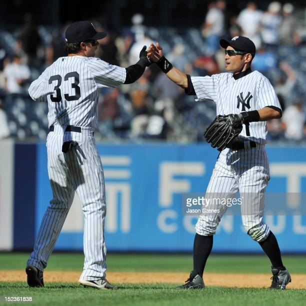 Ichiro Suzuki of the New York Yankees celebrates with his teammate Nick Swisher at the end of their teams ball game against the Toronto Blue Jays...