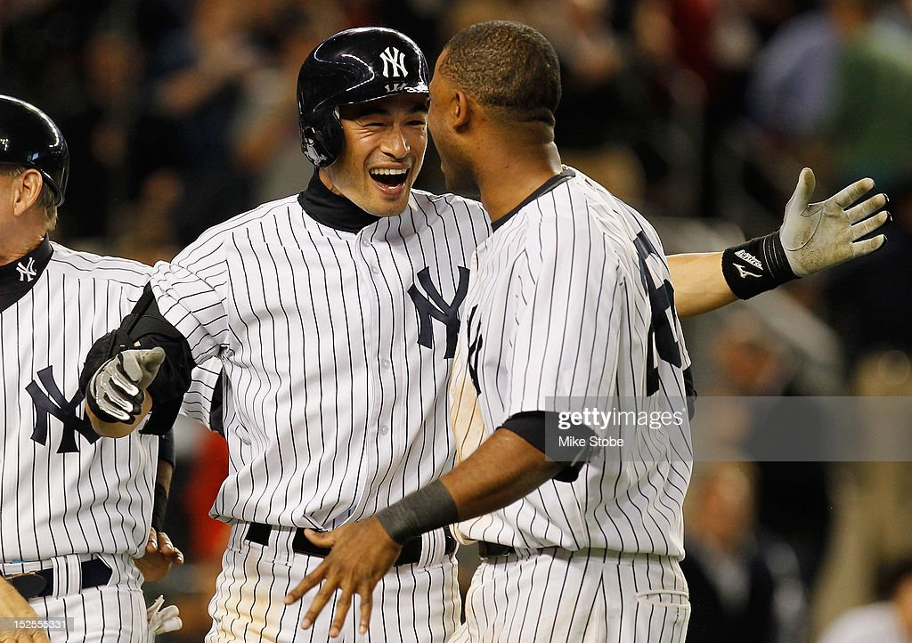 Ichiro Suzuki #31 of the New York Yankees celebrates with teammate Eduardo Nunez #26 after Russell Martin (not pictured) hit a walk-off home run in the 10th inning against the Oakland Athletics at Yankee Stadium on September 21, 2012 in the Bronx borough of New York City. The Yankees defeated the Athletics 2-1.