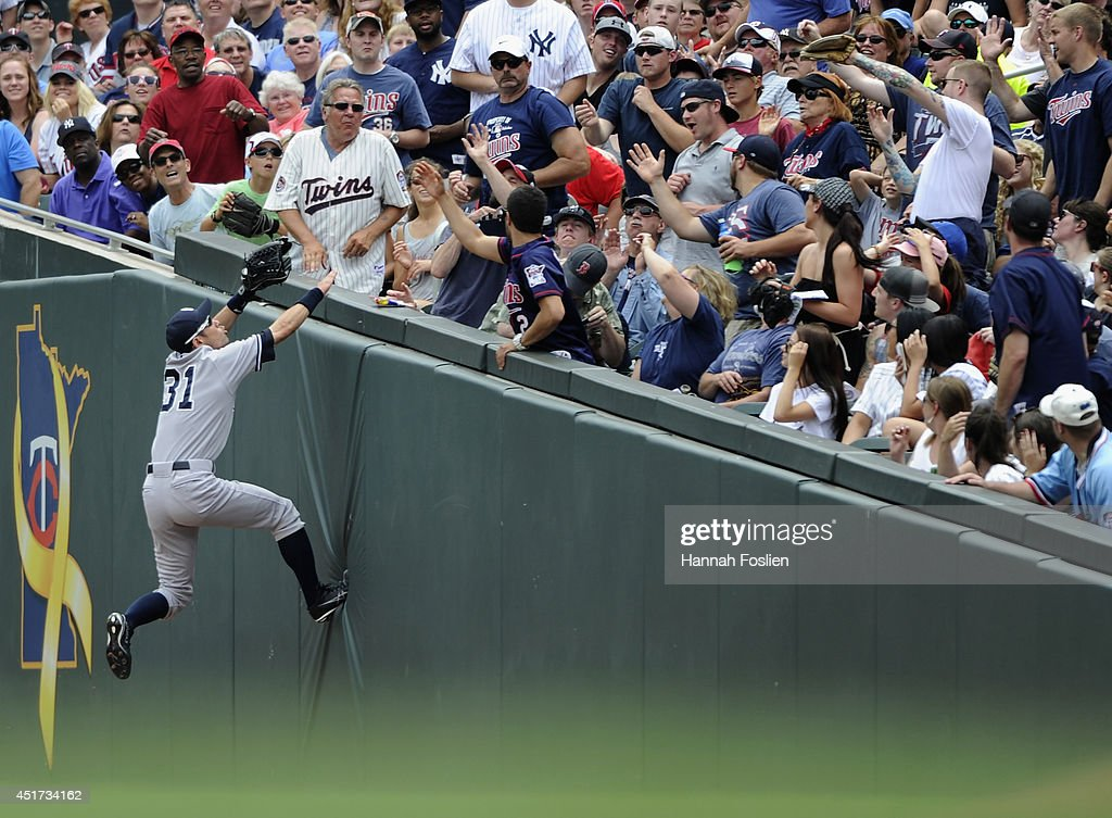 Ichiro Suzuki #31 of the New York Yankees climbs the right field wall going after a foul ball hit by Brian Dozier #2 of the Minnesota Twins during the first inning of the game on July 5, 2014 at Target Field in Minneapolis, Minnesota.