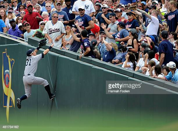 Ichiro Suzuki of the New York Yankees climbs the right field wall going after a foul ball hit by Brian Dozier of the Minnesota Twins during the first...