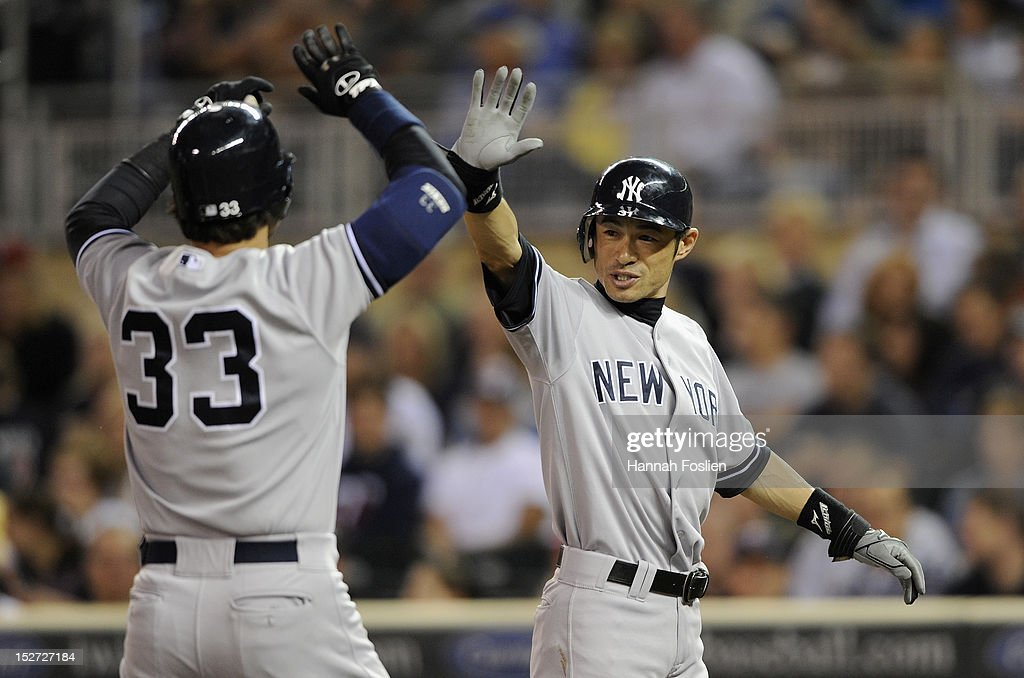 Ichiro Suzuki #31 of the New York Yankees congratulates Nick Swisher #33 on a two run home run during the first inning of the game against the Minnesota Twins on September 24, 2012 at Target Field in Minneapolis, Minnesota.