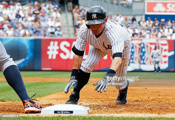 Ichiro Suzuki of the New York Yankees dives back to first base during the third inning against the Detroit Tigers at Yankee Stadium on August 7, 2014...