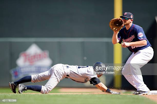 Ichiro Suzuki of the New York Yankees dives back to first base safely as Chris Parmelee of the Minnesota Twins takes the throw during the eighth...