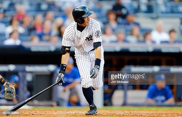 Ichiro Suzuki of the New York Yankees follows through on a fourth inning base hit against the Toronto Blue Jays at Yankee Stadium on September 20...