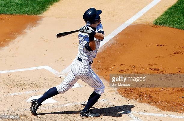 Ichiro Suzuki of the New York Yankees follows through on a fourth inning sacrifice fly against the Minnesota Twins that scored teammate Derek Jeter...