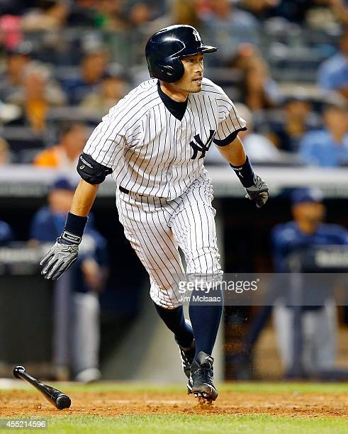 Ichiro Suzuki of the New York Yankees follows through on an eighth inning RBI double against the Tampa Bay Rays at Yankee Stadium on September 10...