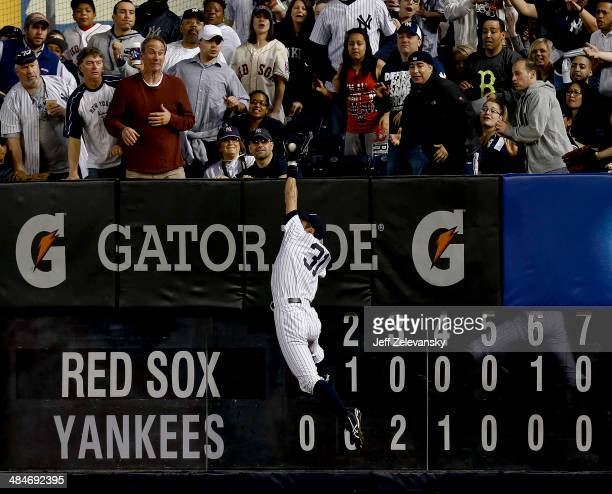 Ichiro Suzuki of the New York Yankees grabs a fly ball off the bat of David Ortiz of the Boston Red Sox at Yankee Stadium on April 13 2014 in the...