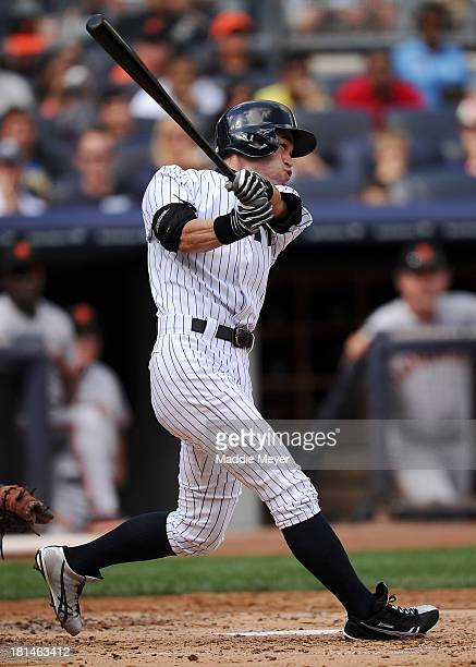 Ichiro Suzuki of the New York Yankees hits a fly ball to center field sending Mark Reynolds in to score against the San Francisco Giants during...