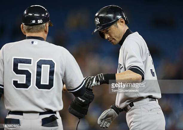 Ichiro Suzuki of the New York Yankees is congratulated by Mick Kelleher after hitting a single in the ninth inning during MLB game action against the...
