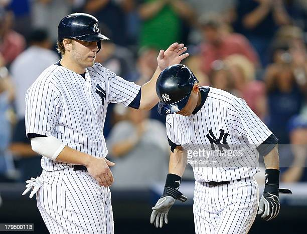 Ichiro Suzuki of the New York Yankees is congratulated by teammate Mark Reynolds after hitting a home run during the fifth inning against the...